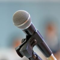 microphone for speaker's speech in the seminar room with audience in the background